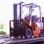 forklift on flat bed truck